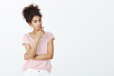 Indoor shot of intense smart cute woman with dark skin and combed hair, holding hand on jaw, frowning and looking aside with focused thoughtful expression, thinking or solving problem Banque d'images