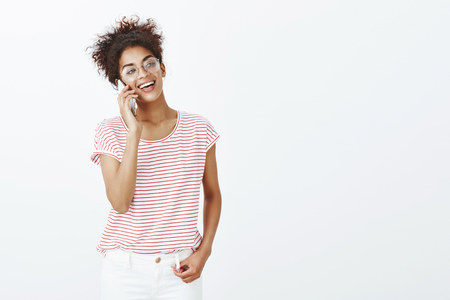 Portrait of talkative good-looking confident woman in glasses and trendy outfit, holding hand on jeans and talking on smarpthone, smiling broadly and gazing aside, enjoying conversation over gray wall