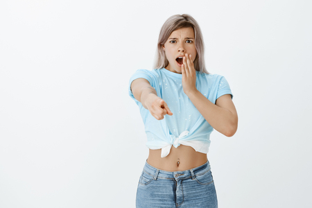 Oh gosh look. Portrait of shocked and stunned charming woman with blond hair and pierced belly, gasping and frowning, dropping jaw while pointing at camera with index finger, being worried and amazed 版權商用圖片