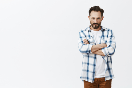 Guy feeling scorn, closing himself from people, standing in defending pose with hands crossed on chest, looking with hate and anger from under forehead at camera, expressing contempt over grey wall