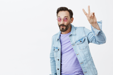 Peace folks. Portrait of middle-aged handsome caucasian man with dark hair and beard, raising hand with peace gesture, smiling and folding lips, being high and having fun on disco party
