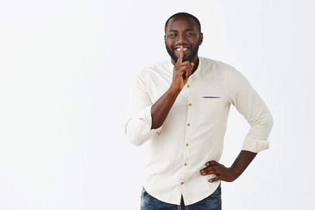 Carefree happy dark-skinned mature male model in trendy shirt, holding hand on waist, smiling joyfully, showing shush gesture with index finger over mouth, keeping secret Stock Photo