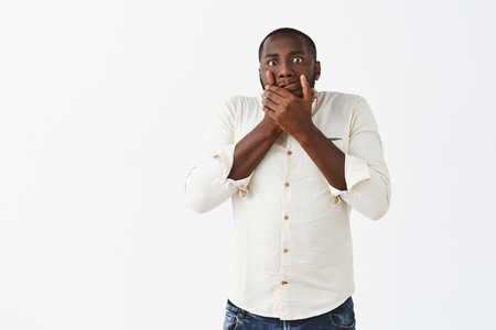 Studio shot of handsome nervous african american man feeling regret saying stupid words, standing shocked and stunned, covering mouth with palms and gazing worried at camera over grey wall Stock Photo - 107406125