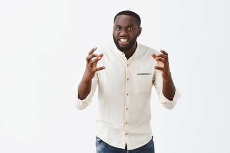Outraged dangerous African American guy in white shirt, raising hands and clenching it in fists, grimacing with clenched teeth, showing anger and loosing temper Stock Photo - 107406162