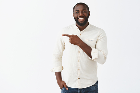 Stylish and successful dark-skinned male entrepreneur in white shirt showing office of company, leading the way, pointing left to indicate at desk of new employee, smiling friendly over grey wall Stock Photo - 107406175