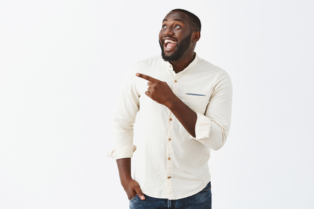 Man being surrpsied with amazing fireworks in his honor, celebrating b-day with friends. Joyful handsome african american guy with beard in white shirt pointing and gazing happily at upper left corner Stock Photo - 107406177