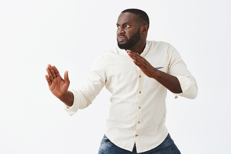 Funny and playful adult African American guy with beard, standing in profile in martial arts pose with raised palms, frowning and staring left with angry and evil expression to fight with enemy Stock Photo - 107406180