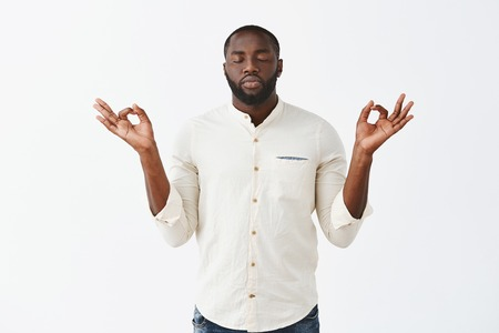 Reuniting with anture through meditation. Calm good-looking african american male in white casual shirt, raising hands in zen gesture, closing eyes and standing with calm expression over grey wall Stock Photo - 107406183