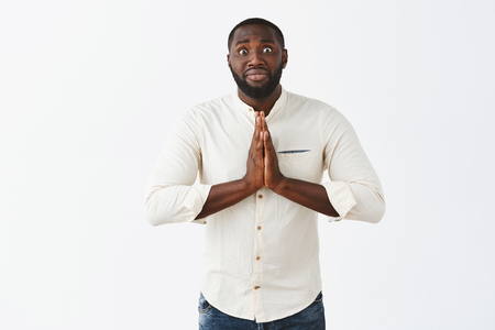 Man really need help asking favour from friend feeling intense and nervous. Funny African American guy in white shirt, holding hands in pray near chest, staring with popped eyes at camera, begging Stock Photo - 107406185