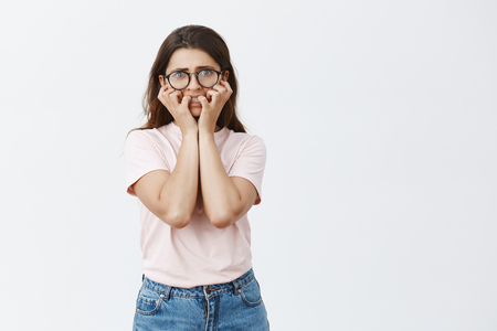 Indoor shot of woman being frightened of deadlines to death. Portrait of nervous panicking smart nerdy female in black large glasses biting fingernails and staring scared at camera over gray wall Stock Photo - 107406027