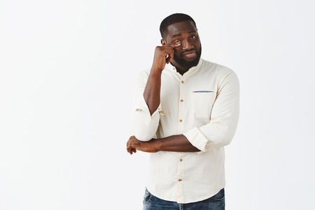 Masculine handsome bearded African American male model in white shirt whipping teardrop from eye after watching dramatic film and being touched to tears over grey wall. Even strongest cry sometime Stock Photo - 107406028