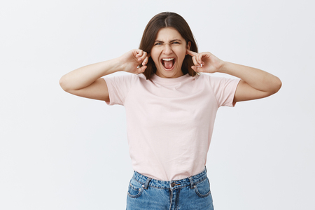 Studio shot of intense displeased attractive caucasian feminine woman in stylish outfit closing ears with index fingers and yelling being annoyed with loud noisy music asking brother turn sound off Stock Photo - 107406032
