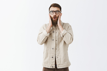 Studio shot of emotive shocked and worried male model with long beard in glasses holding hands on face looking nervous and shook learning terrifying bad news expressing empathy while in stupor Stock Photo - 107406039