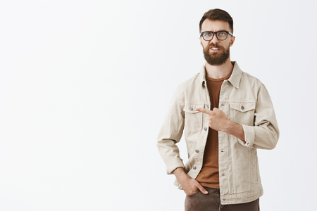 Studio shot of intense unsure and dissatisfied handsome caucasian guy with long brown beard and hairstyle expressing scron lifting upper lip with disdain pointing left being angry, showing dislike