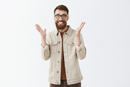 Excitement raising higher. Portrait of excited and shocked panicking caucasian guy with long beard in hipster black glasses shaking raised palms clenching teeth frowning looking worried over gray wall Stock Photo - 107405964