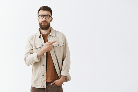 Portrait of intense shocked and worried hipset man with long brown beard in black stylish glasses and beige jacket pointing right frowning being nervous finding out shook news, expressing empathy Stock Photo - 107405967