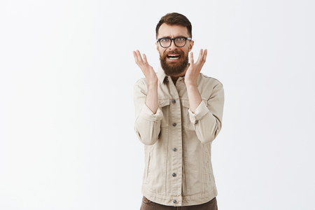 Pissed disstressed and annoyed adult hipster guy with long beard in black trendy glasses and beige jacket frowning raising palms in anger hearing nonsense and being mad with stupid conversation Stock Photo - 107405968