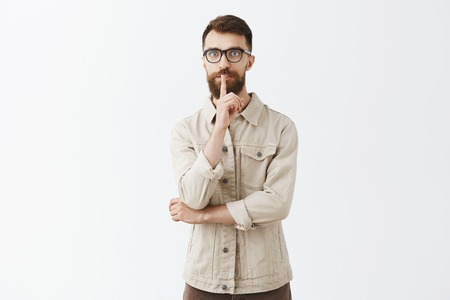 Worried and intense good-looking bearded guy in black glasses and beige jacket feeling nervous, hiding mistake from boss asking coworker keep silence, not tell secret saying shh showing shush gesture Foto de archivo