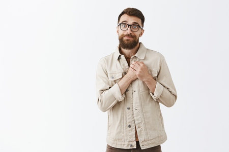 Silly and cute handsome masculine guy with long beard in black prescribed glasses holding palms together on heart smiling and gazing with grateful loving and caring expression over gray wall Stock Photo - 107405973