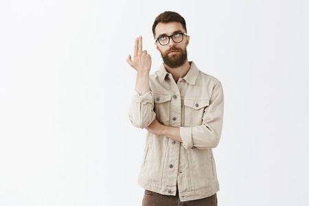 Man dying from boredom. Annoyed and displeased good-looking mature husband with long beard in black trendy glasses and outdoor jacket rolling eyelids up and showing gun with fingers as if blowing head Stock Photo - 107405975