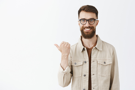 Let me show you company products. Portrait of handsome mature and masculine brunet with long beard in glasses wearing casual beige jacket pointing left with thumb and smiling friendly at camera Stock Photo - 107405976