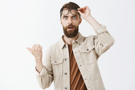 Waist-up shot of concerned questioned handsome mature male with beard taking off glasses staring shocked and stunned at camera pointing left with thumb standing impressed over gray background Stock Photo - 107405977