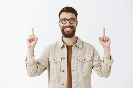 Friendly delighted and thrilled handsome funny brunet with long beard in glasses and beige jacket raising index fingers in sky pointing up with satisfied grin standing over gray background Stock Photo - 107405981