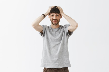 Portrait of confused and insecure attractive European man with stylish beard and hairstyle holding hands on head, standing in stupor facing problematic decision Stock Photo - 107405880