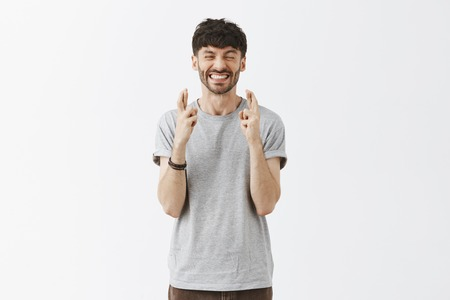 Man putting all faith in making wish. Portrait of excited and intense good-looking urban european guy with stylish hairstyle clenching teeth and smiling while crossing fingers for good luck Stock Photo - 107405883