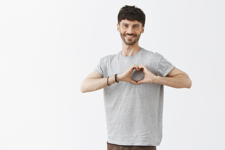 Dpreading love and care across office. Portrait of joyful and stylish hipser dark-haired guy with beard in casual clothes showing heart over chest and smiling, expressing affection and tender feelings Stock Photo - 107405884