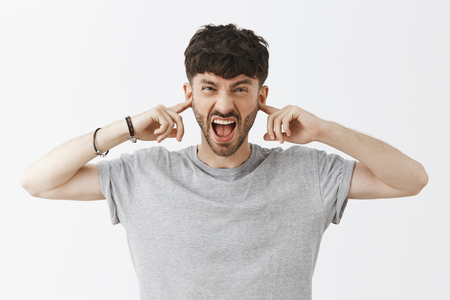 Cannot stand noisy places. Displeased pissed and bothered male neighbour with dark hair and beard, screaming or yelling covering ears with index fingers like earplugs, demanding turn sound off Stock Photo