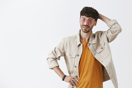 Indoor shot of stylish adult caucasian man in trendy sunglasses yellow t-shirt and shirt scratching head and looking confused and uncertain at camera having doubts over gray background Stock Photo