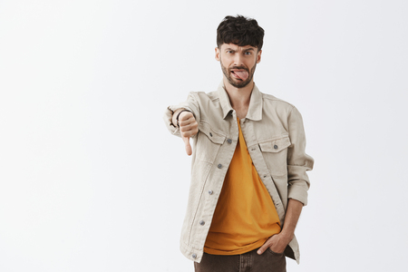 Displeased childish and emotive handsome modern male with beard in shirt over yellow t-shirt holding hand in pocket, showing thumb down, sticking out tongue from displeasure Stok Fotoğraf