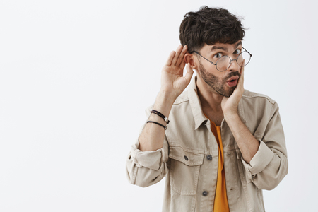 Wow tell me all dirty details of recent rumor. Intrigued good-looking stylish office worker in glasses and trendy beige shirt with beard holding palm near folded lips and hand near ear gossiping