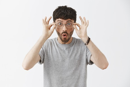 Waist-up shot of impressed and amazed handsome young male programmer in grey t-shirt touching glasses and saying wow with folded lips from amazement and excitement seeing incredible deal Archivio Fotografico