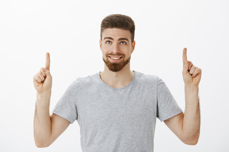 Waist-up shot of handsome masculine man with blue eyes and beard smiling joyfully and self-assured raising hands looking and pointing up delighted and happy standing pleased over gray background