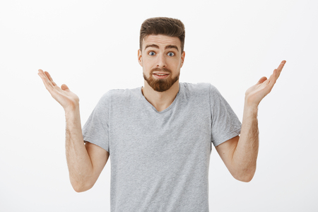 Studio shot of clueless unaware handsome bearded man shrugging with raised hands and eyebrows making silly clueless expression cannot answer question being confused over gray background