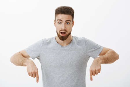 Guy learned how gig economy works being amazed and intrigued posing in grey t-shirt looking at camera shocked with opened mouth pointing down being questioned and surprised over white wall