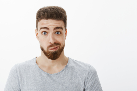 Portrait of silly and funny handsome man with beard, moustache and blue eyes smirking making uncertain awkward face looking in mirror and thinking about making changes posing against gray background
