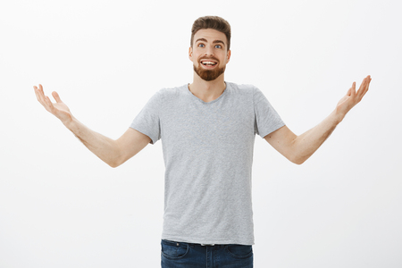 Portrait of amazed and excited surprised european man with beard and raising hands to air looking joyful and thankful giving thanks to God for helping him fulfill desires and dreams over gray wall