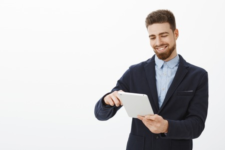 What pleasure looking at bank account full of money. Delighted handsome and successful businessman with beard and neat hairstyle in suit holding digital tablet smiling pleased looking at device screen Reklamní fotografie