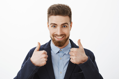 Energized good-looking and assured successful man with beard and blue eyes in stylish formal suit showing thumbs up being assured plan work great standing self-assured against gray background