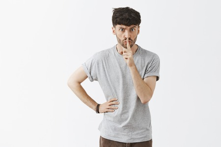 I order you keep quiet. Serious displeased and strict aduly male teacher with stylish hairstyle and beard saying shh while showing shush gesture with index finger over mouth demanding silence