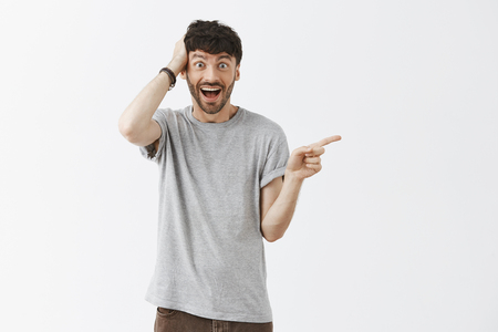 No way it cannot be true. Portrait of amazed and thrilled happy and excited good-looking young artistic guy in grey t-shirt holding hand on head and pointing right over gray background