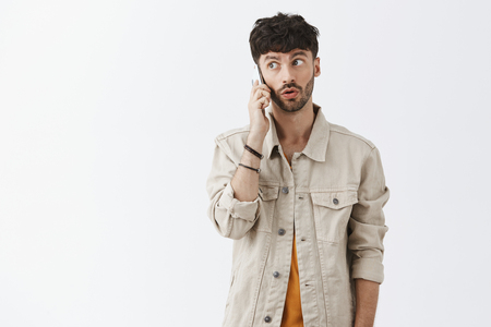 Man feeling intrigued hearing interesting offer via smartphone listening carefully while talking on cellphone gazing left posing with phone near ear and folded lips over gray background