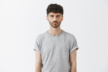Waist-up shot of serious-looking unemotional good-looking adult man in gray t-shirt looking at camera calm and strict, being snob and hard to impress standing over gray background Stok Fotoğraf