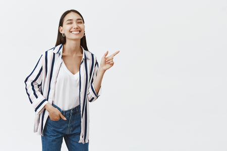 Studio shot of carefree emotive and friendly famous woman in stylish striped blouse, bending and pointing right with index finger, holding hand in pocket and smiling broadly from happiness