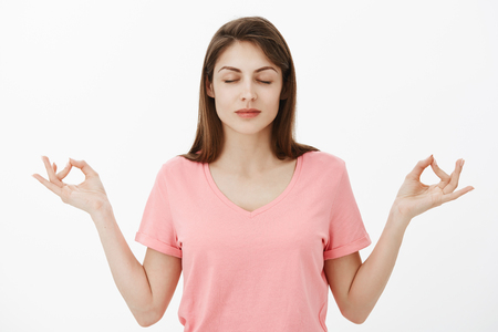 Girl inhales air and relaxes. Calm and relieved attractive young woman in pink t-shirt, standing with closed eyes and spread hands with zen gesture during meditation practice or yoga lesson Stock Photo
