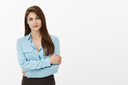 Portrait of smart confident female entrepreneur in blue blouse, hugging herself with hands on chest, smiling, feeling tired while working in office, listening client complaints over gray background