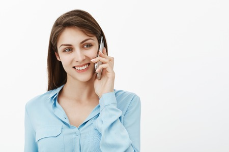 Girl calling mother from work. Portrait of positive happy cute female coworker in blue blouse, holding smartphone new ear, gazing aside and smiling, talking with friend and enjoying nice conversation Stock Photo